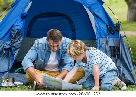 Father and son camping and looking for their way home on a sunny day - stock photo