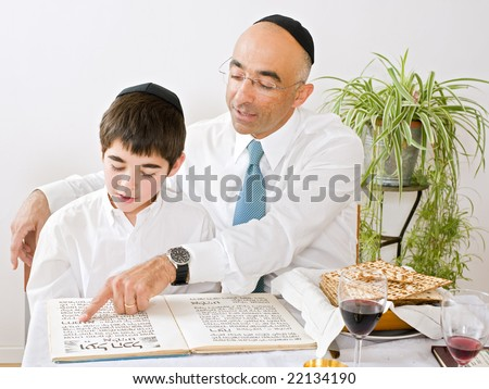 father and son celebrating passover reading the Haggadah - stock photo