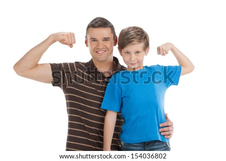 Father and son. Cheerful father and son standing close to each other and showing their musculature while isolated on white - stock photo