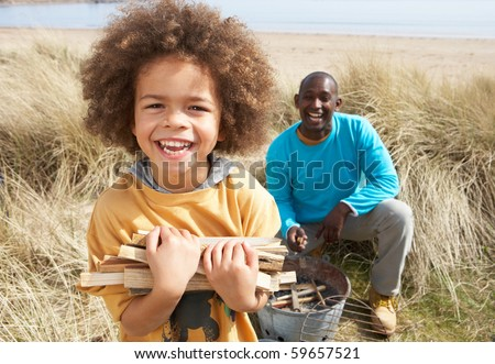 Father And Son Collecting Firewood On Beach Camping Holiday - stock photo