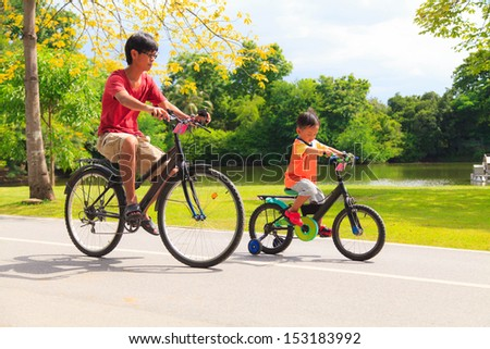 Father and son cycling in the park - stock photo