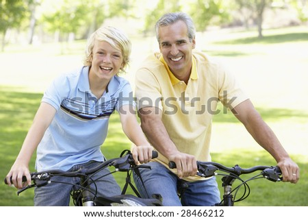 Father And Son Cycling Through A Park - stock photo