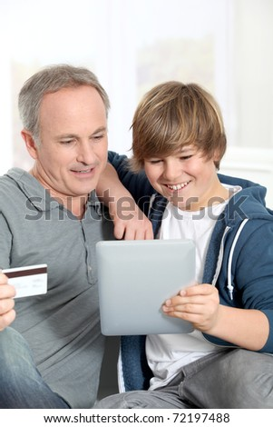 Father and son doing online shopping - stock photo