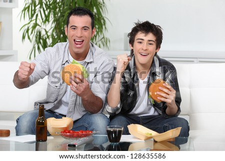 Father and son eating burgers in front of TV - stock photo