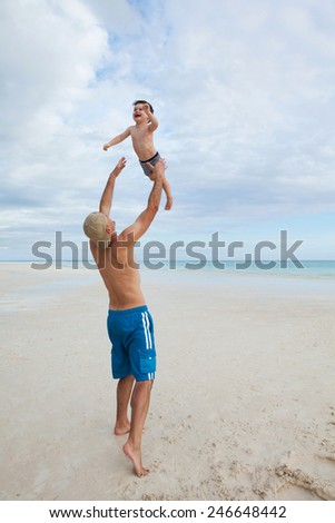 Father and son enjoy summer day at tropical beach. - stock photo