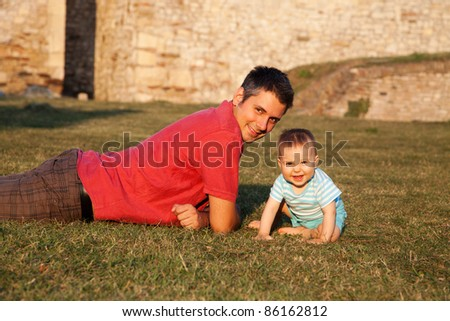 Father and son enjoying afternoon sunshine - stock photo