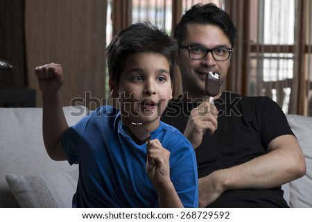 Father and son enjoying chocolate-coated blocks of ice cream on stick. - stock photo