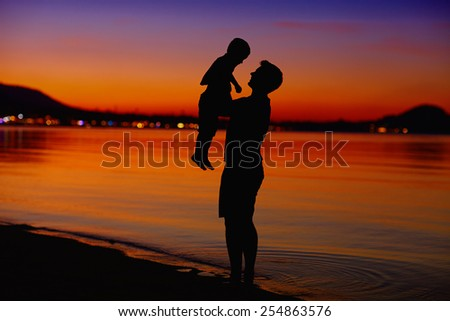 father and son enjoying life at sunset - stock photo