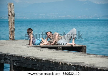 Father and son enjoying summer vacation on sea dock