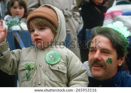 Father and son enjoying the 1987 St. Patrick's Day Parade, NY City - stock photo
