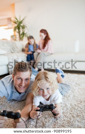 Father and son enjoying video games together in the living room - stock photo