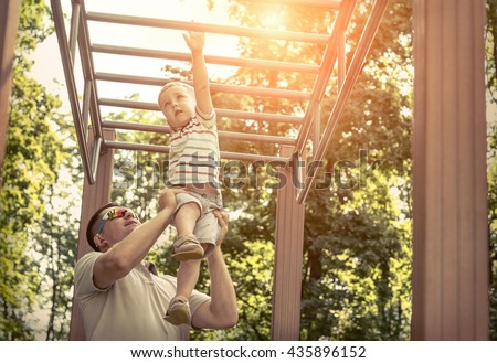 Father and son exercising outdoor. - stock photo