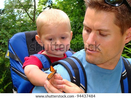 Father and son exploring nature - looking at insects in the forest