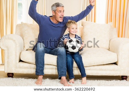 Father and son exulting on the sofa while holding football ball - stock photo