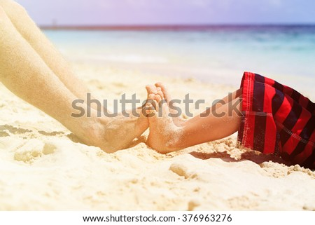 father and son feet on summer beach - stock photo