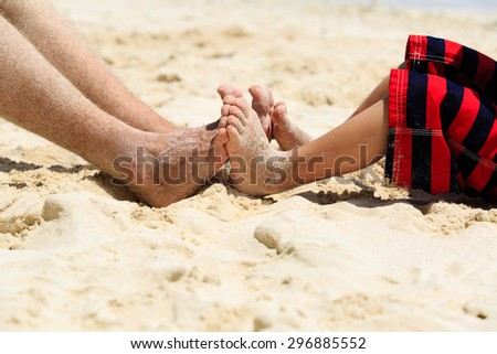 father and son feet on summer beach, family relax - stock photo