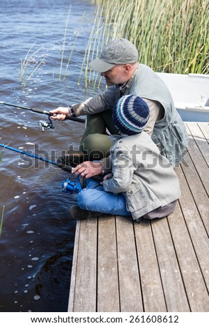 Father and son fishing at a lake in the countryside - stock photo