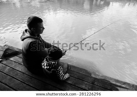 Father and son fishing. Fishing on the lake. AREA fishing. Trout fishing. Active family vacation. The relationship between father and son. - stock photo