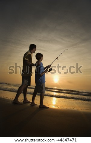 Father and son fishing in ocean surf at sunset.  Vertically framed shot. - stock photo