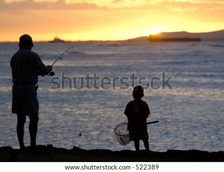 Father and son fishing just at sunset. - stock photo