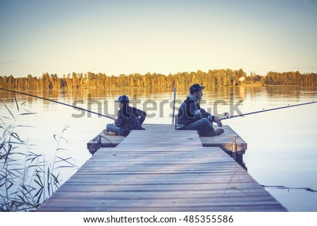 Father and son fishing on autumn lake