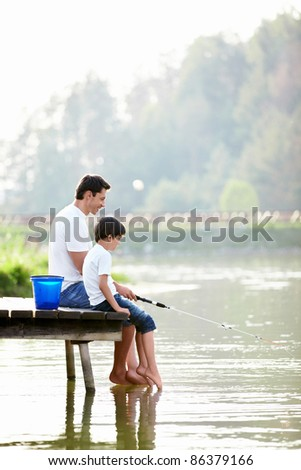 Father and son fishing on the lake - stock photo