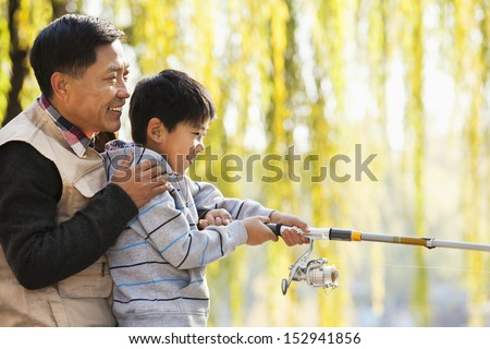Father and son fishing together at lake - stock photo