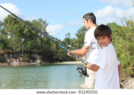 Father and son fishing together in the summertime - stock photo
