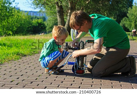 father and son fixing bike in summer park - stock photo