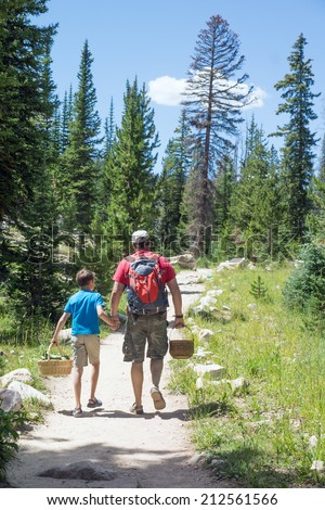 Father and son go hand in hand along the trail into the woods in search of mushrooms. Uinta Wasatch Cache National Forest, Utah - stock photo