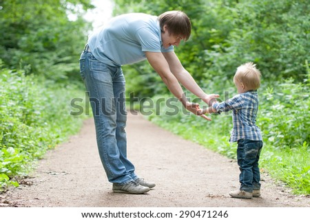 Father and son go in a park. Father gives hand the son - stock photo
