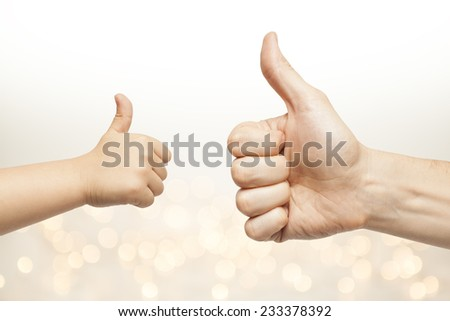 father and son hands giving like on christmas lights background  - stock photo