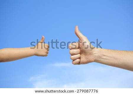 father and son hands giving like on sky with clouds background - stock photo