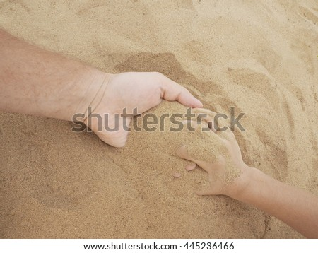 Father and son hands on sand. Close up . - stock photo