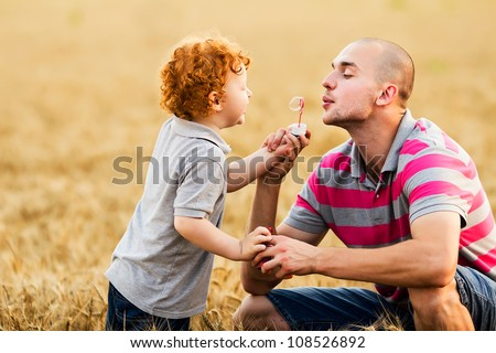 Father and son having a good time outdoor in wheat field - stock photo