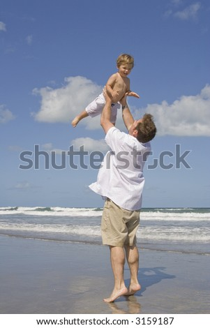 Father and son having fun on a beach - stock photo