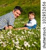 Father and son having fun on meadow - stock photo