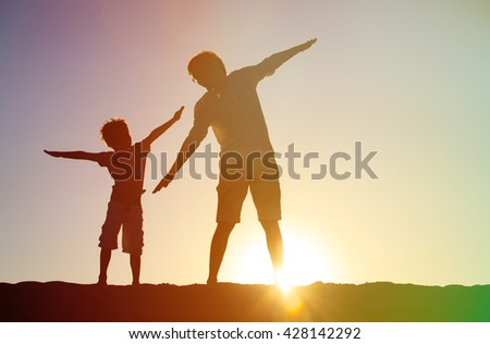 father and son having fun on sunset - stock photo