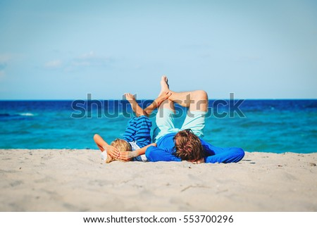 father and son having fun on the beach