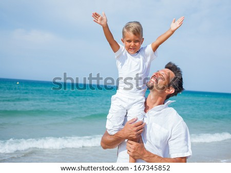 Father and son having fun on tropical beach