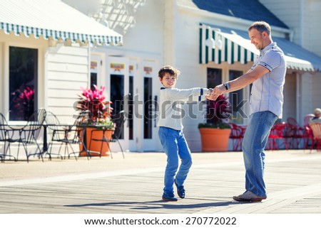 Father and son having fun outdoors in city during his summer vacation - stock photo