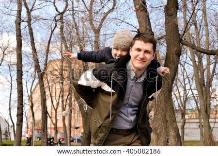 Father and son having fun outdoors on a spring sunny day. Happy smiling little boy in the arms of his dad. Concept of happy family life, love and happiness.  - stock photo