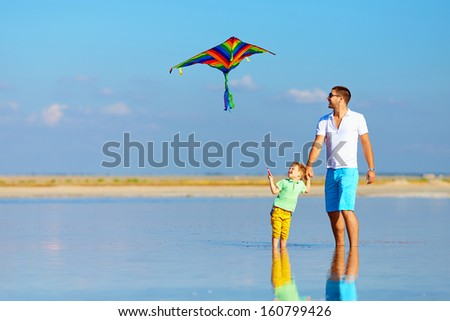 father and son having fun, playing with kite together