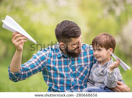 Father and son having fun together in summer park. - stock photo