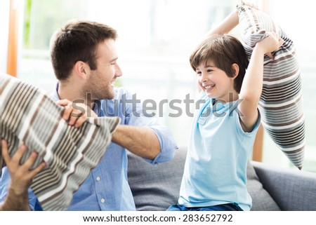 Father and son having pillow fight  - stock photo