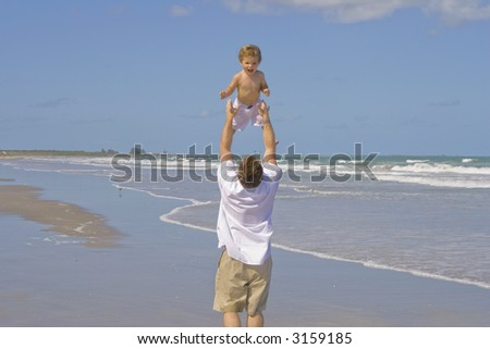 Father and son heaving fun on a beach - stock photo