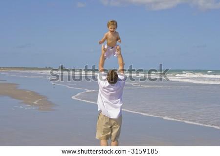 Father and son heaving fun on a beach - stock photo