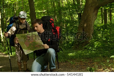 Father and son hiking in forest. Looking at map.