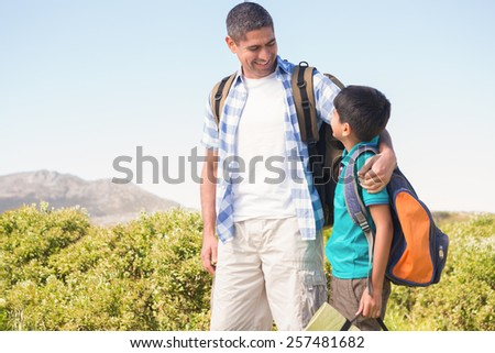 Father and son hiking in the mountains on a sunny day - stock photo