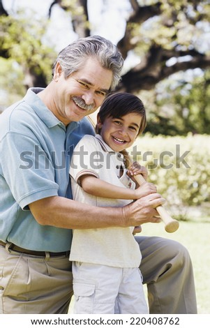 Father and son holding baseball bat - stock photo